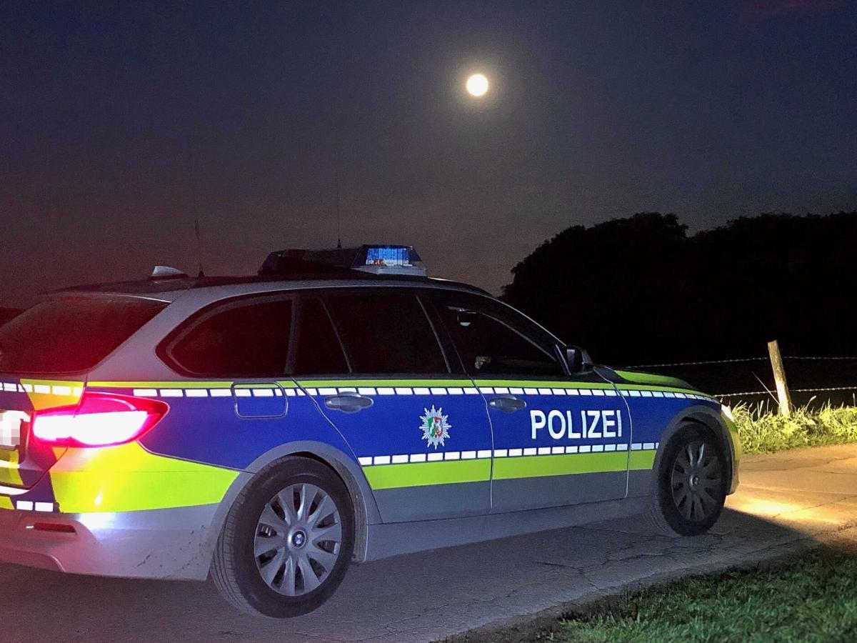 Ein beleuchtetes Polizeiauto auf einem schmalen Weg in der Nacht. Darüber der Vollmond. Das Bild zeigt einen BMW Streifenwagen aus NRW. Man kann nicht erkennen, wo er sich befindet. Im Hintergrund steht ein Weidezaun. Offenbar ist es eine ländliche Umgebung.